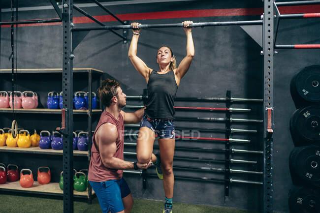 Serious sudorosa deportista muscular con instructor ayudando a realizar pull-ups en el gimnasio mirando hacia otro lado - foto de stock