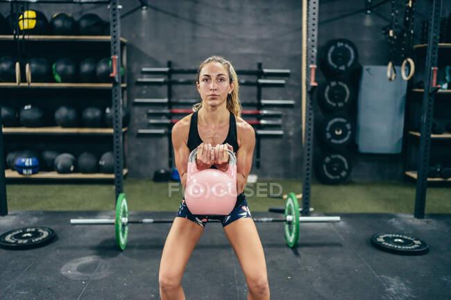 Впевнена спортсменка в спортивній манері робить вправи з важким кетлебелем і насосом м'язів, дивлячись на камеру. — Stock Photo