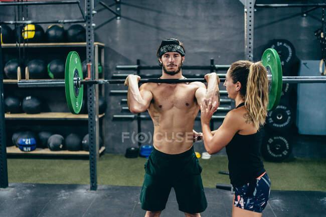 Сильный тренер в спортивной одежде, помогающий спортивному клиенту и занимающийся спортом в современном спортзале — стоковое фото