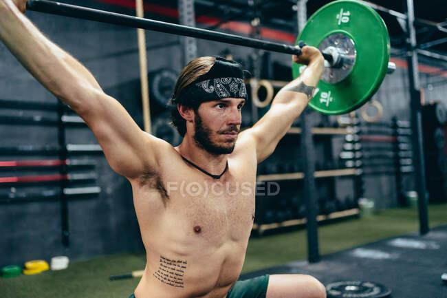 Бічний вид спортсмена з сильним тулубом сидить у спортзалі і готується до важкої атлетики з важким барилом, дивлячись у бік — Stock Photo