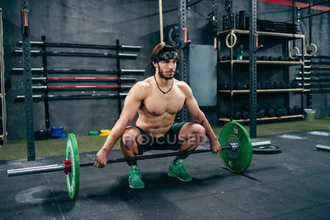 Спортсмен з сильним тулубом, що сидить у спортзалі і готується до важкої атлетики з важким барилом, дивлячись у бік — стокове фото