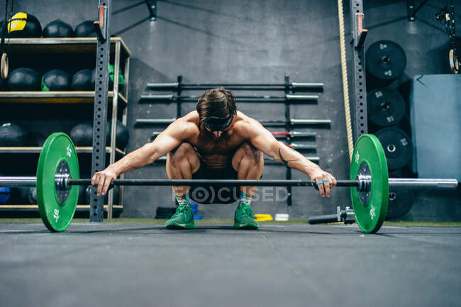 Ground level of fit sportsman with strong torso squatting in gym and preparing for weightlifting exercise with heavy barbell — Stock Photo