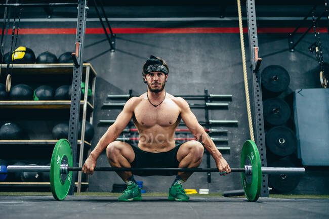 Fit sportsman with strong torso squatting in gym and preparing for heavy lifting exercise with heavy barbell looking away — стоковое фото