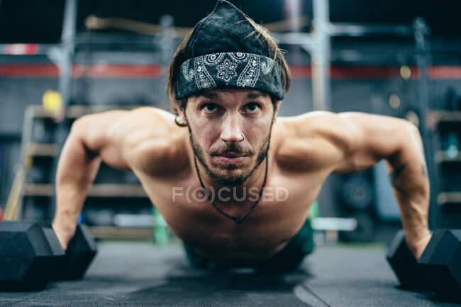 Сильний спортсмен - без сорочки штовхає глядачів і під час тренувань у спортзалі та озирається. — стокове фото
