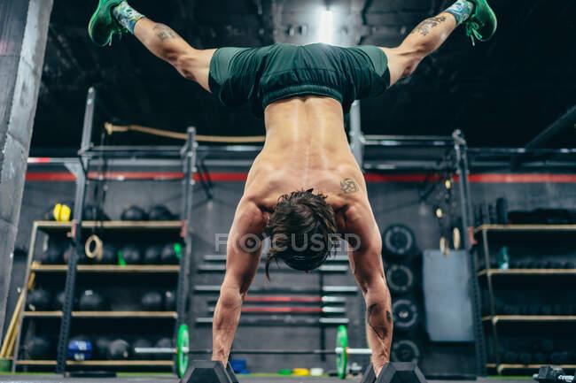 Низкий угол обзора анонимного спортсмена с обнаженным туловищем, балансирующим вверх ногами на гирях во время тренировки в спортзале — стоковое фото