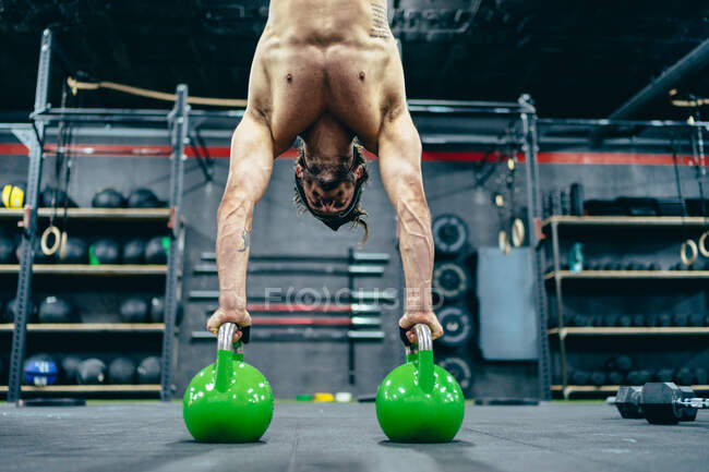 Низкий угол у спортсмена с обнаженным туловищем, балансирующим вверх ногами на гирях во время тренировки в спортзале — стоковое фото