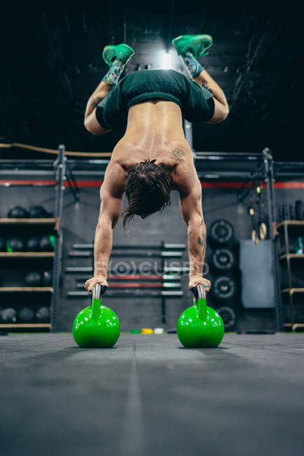 Low angle back view of anonymous male athlete with naked torso balancing upside down on kettlebells during training in gym — Stock Photo