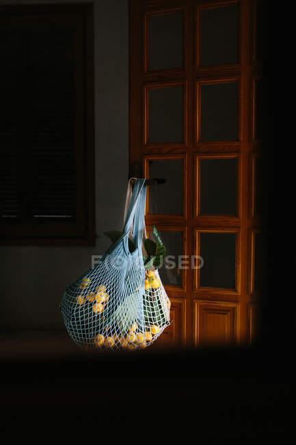 Bolsa de hilo blanco con fruta fresca de níspero y hojas colgando en la puerta - foto de stock
