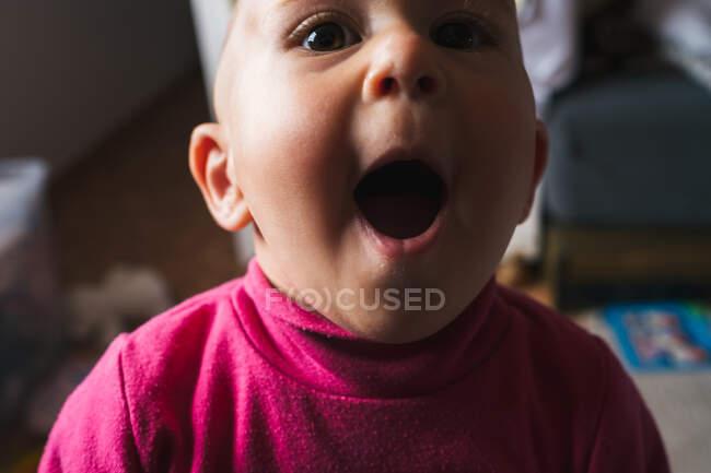 Crop stupito bambino in camicia rosa seduto sul pavimento con la bocca aperta mentre gioca a casa e guardando la fotocamera — Foto stock