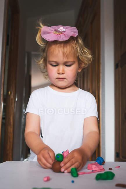 Милый веселый малыш в повседневной одежде играет с пластилином, проводя время вместе дома — стоковое фото