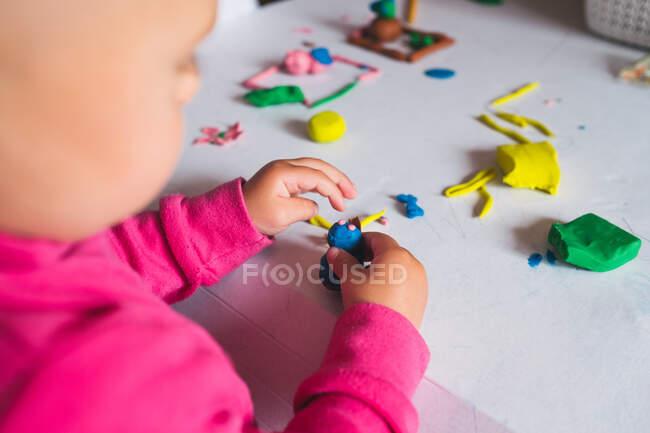 Dall'alto vista di un bambino irriconoscibile che gioca con argilla modellante colorata su un tavolo bianco a casa — Foto stock