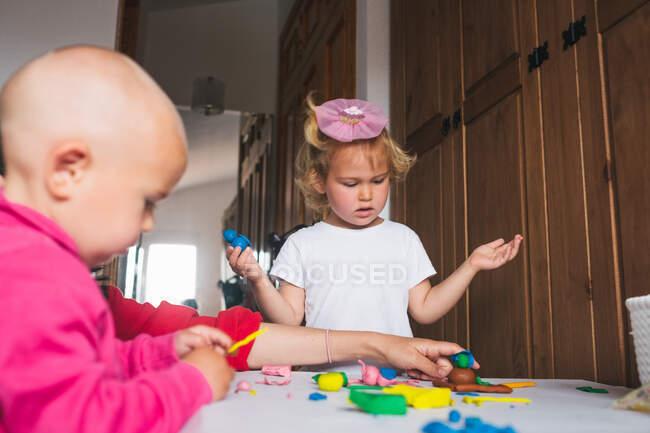 Carino allegri bambini in abiti casual giocare con la plastilina mentre trascorrono del tempo insieme a casa — Foto stock