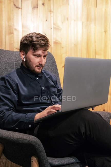 Entrepreneur mâle assis à la table en bois dans l'espace de travail créatif et de travailler sur un projet à distance tout en utilisant netbook — Photo de stock