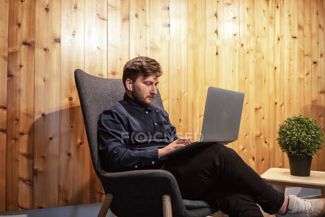 Imprenditore maschio seduto al tavolo di legno in uno spazio di lavoro creativo e che lavora su un progetto remoto durante l'utilizzo di netbook — Foto stock
