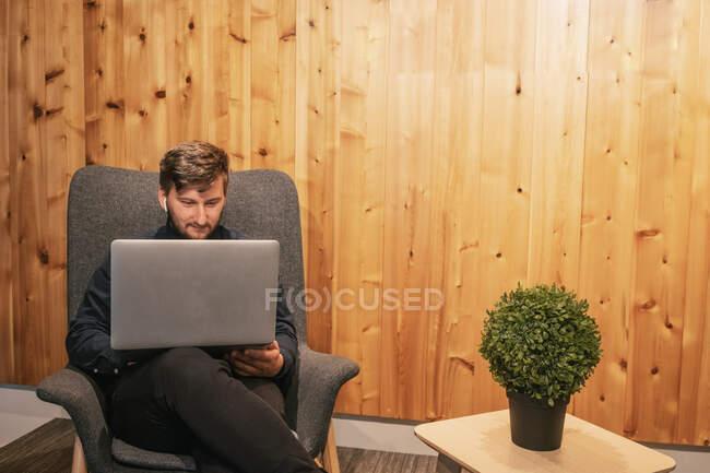 Мужчина-предприниматель сидит за деревянным столом в креативном рабочем пространстве и работает над удаленным проектом при использовании нетбука — стоковое фото
