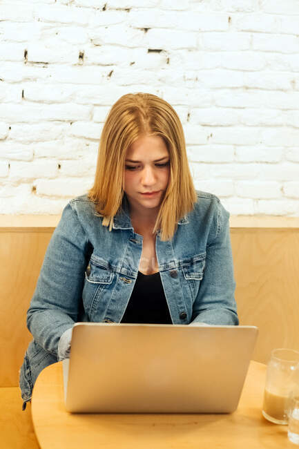 Concentrated self employed female in casual clothes sitting at table in bright workspace and typing on netbook during remote work — Stock Photo