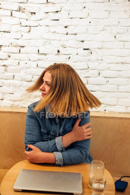 Happy female freelancer in casual shirt relaxing at table in modern workspace while having break during distant work — Stock Photo