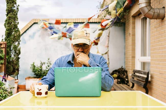 Hombre anciano reflexivo en gorra y camisa de mezclilla que se centra en la pantalla con interés mientras está sentado en la mesa con taza de bebida sabrosa y el uso de netbook en el patio de la casa de campo - foto de stock