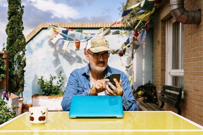 Thoughtful senior male in cap and browsing smartphone while sitting at laptop with mug of yummy hot drink in backyard of country house in sunny day — Stock Photo