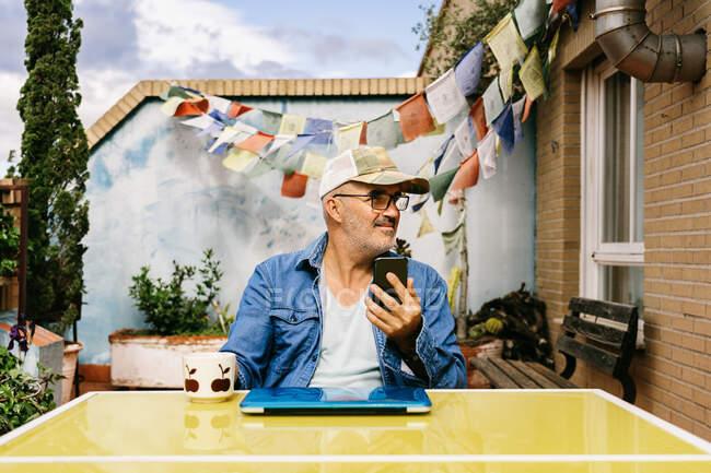 Pensativo hombre mayor en la tapa y el teléfono inteligente de navegación mientras está sentado en el ordenador portátil con taza de deliciosa bebida caliente en el patio trasero de la casa de campo en el día soleado - foto de stock