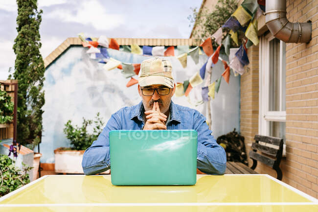 Thoughtful elderly male in cap and denim shirt focusing on screen with interest while sitting at table with mug of tasty beverage and using netbook in yard of country house — Stock Photo