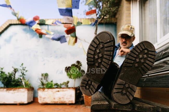 Низкий угол спокойного задумчивого пенсионера в повседневной одежде и сапогах, отдыхающего в одиночестве на деревянной скамейке против зеленых цветов, растущих в клумбах на террасе коттеджа в пригороде — стоковое фото
