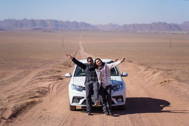 Удаленный вид веселых юношей и девушек в повседневной одежде, наслаждающихся приключениями во время путешествия по пустыне у подножия гор — стоковое фото