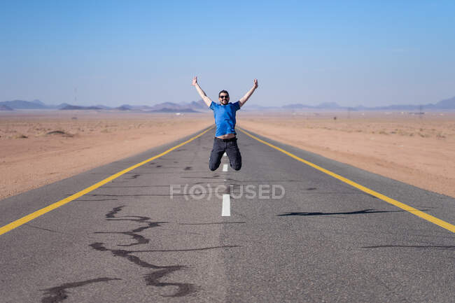 Cheerful man in casual clothes enjoying freedom and adventure during traveling while leaping up on empty road in desert valley with mountains on horizon — Stock Photo