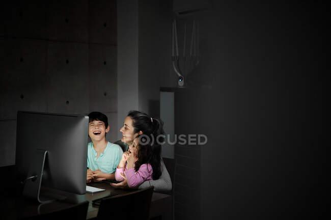 Счастливая молодая мать с маленьким сыном и дочерью держат смартфон, сидя вместе за столом с компьютером и смотреть смешное видео в темной комнате дома — стоковое фото