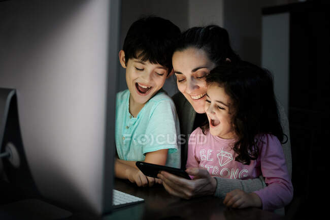 Happy young mother with little son and daughter holding smartphone while sitting together at table with computer and watching funny video in dark room at home — Stock Photo