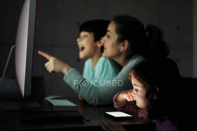 Happy young mother with little son and daughter sitting together at table with computer at home — Stock Photo