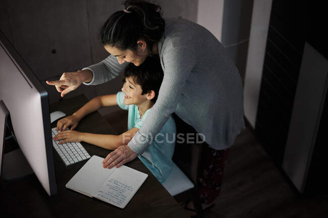 Side view of young woman explaining study task to positive son sitting at table with computer and textbook during online lesson at home — Stock Photo