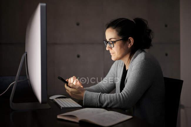 Сторона зору серйозно сконцентрована молода жінка в повсякденному одязі і окуляри сидять за столом з комп'ютером з білим пропущеним екраном і переглядають смартфон, працюючи віддалено ввечері вдома. — стокове фото