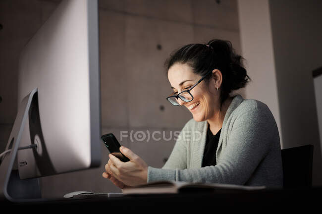 Side view of serious concentrated young female in casual wear and eyeglasses sitting at table with computer with white blank screen and browsing smartphone while working remotely at evening time at home — Stock Photo