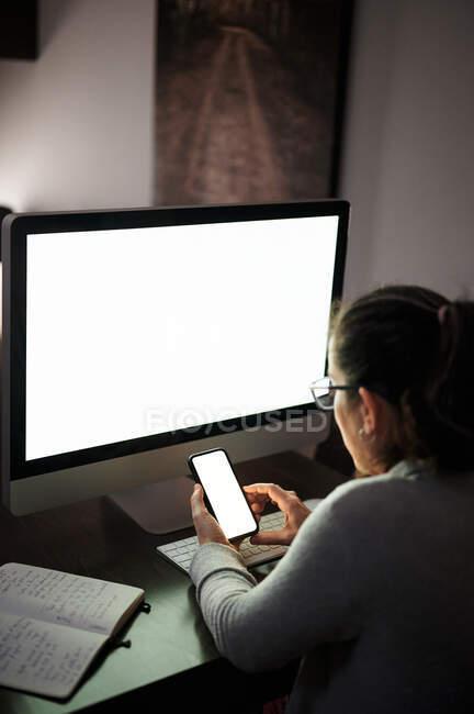 Vista lateral de una mujer joven concentrada grave en ropa casual y anteojos sentados en la mesa con computadora con pantalla blanca en blanco y teléfono inteligente de navegación mientras trabaja de forma remota por la noche en casa - foto de stock