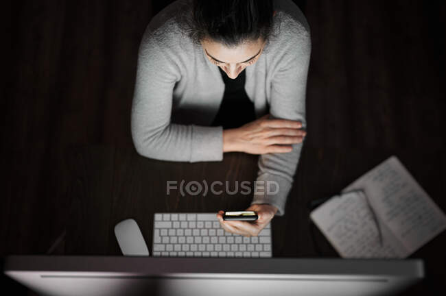 Young female in casual wear and eyeglasses sitting at table with computer with white blank screen and browsing smartphone while working remotely at evening time at home — Stock Photo