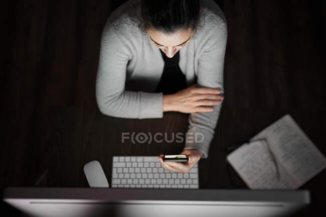Молода жінка в повсякденному одязі і окулярах сидить за столом з білим екраном і переглядає смартфон, працюючи віддалено ввечері вдома. — стокове фото