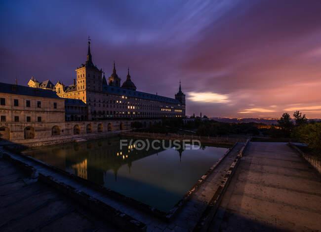 Перед історичним палацом з освітленими вікнами і ставок під час дивовижного заходу сонця увечері. — стокове фото