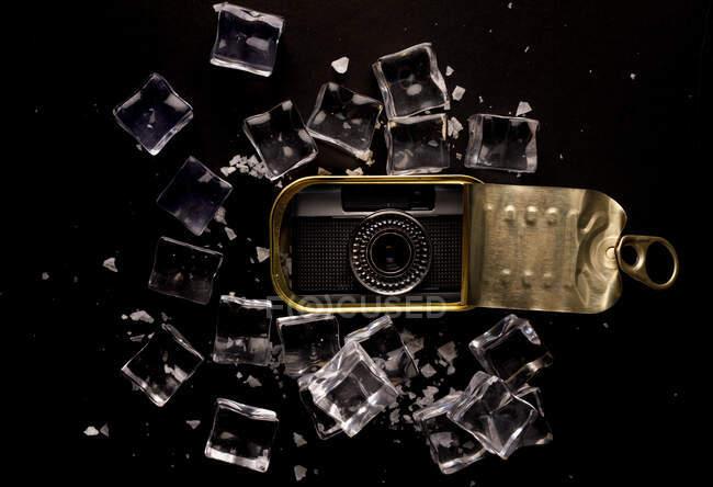 Сверху ретро фотокамера размещена в металлической банке на черной поверхности с разбросанными кубиками льда, демонстрирующими концепцию хорошо сохранившегося гаджета — стоковое фото