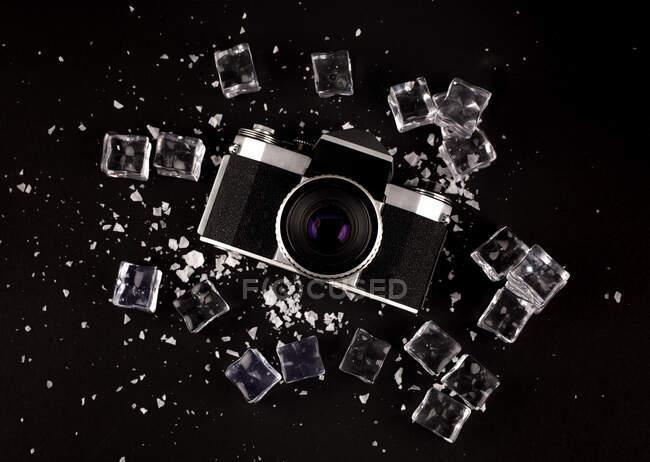 Vista superior de la cámara de fotos vintage rodeada de cubitos de hielo que muestran el concepto de gadget bien conservado sobre fondo negro - foto de stock