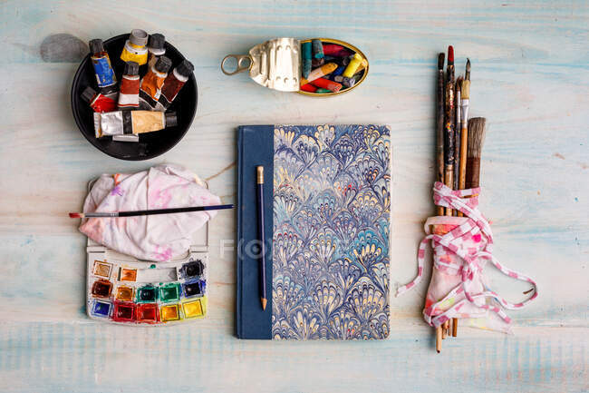 Top view of creative sketchbook and paintbrushes arranged on table with watercolor and pastel colors — Stock Photo