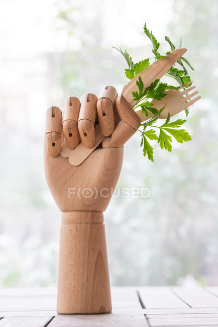 Creative mannequin hand with disposable fork and knife garnished with sprig of green parsley placed on table in garden — Stock Photo