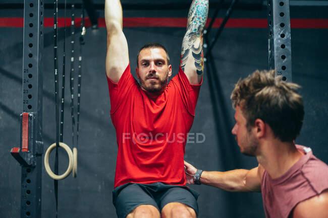 Deportista masculino determinado en pantalones cortos deportivos y camiseta haciendo ejercicios en el travesaño y los músculos de bombeo bajo supervisión del entrenador - foto de stock