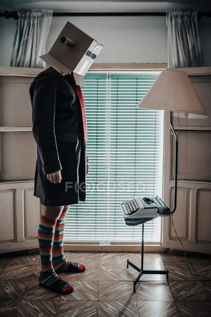 Man wearing cardboard box and striped socks standing by retro typewriter — Stock Photo