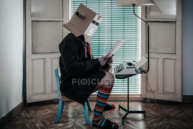 Чоловік у картонній коробці і смугасті шкарпетки сидять на кріслі з друкарською машинкою і читають папір — стокове фото