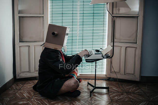 Man wearing cardboard box and striped socks sitting on floor typing on retro typewriter — Stock Photo