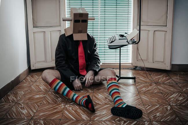 Чоловік у картонній коробці і смугасті шкарпетки сидять на підлозі біля стільця з друкарською машинкою ретро — стокове фото