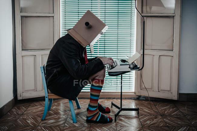 Man wearing cardboard box and striped socks sitting on chair typing on retro typewriter — Stock Photo