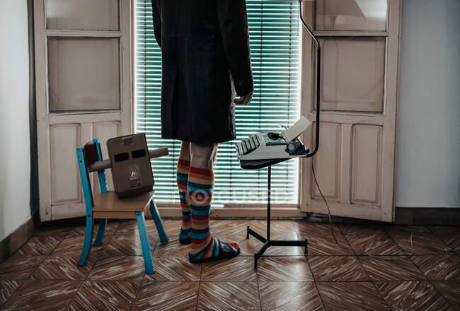 Обрезанный снимок человека с картонной коробочной маской в полосатых носках, стоящих на ретро-машинке — стоковое фото