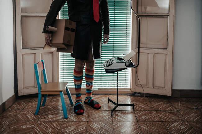 Tiro recortado del hombre con la máscara de la caja de cartón con calcetines a rayas de pie por la máquina de escribir retro - foto de stock